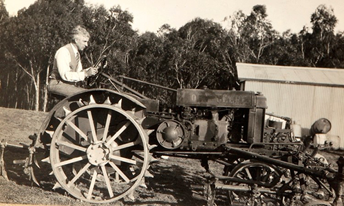 Theo Brown in a black and white photo on a tractor