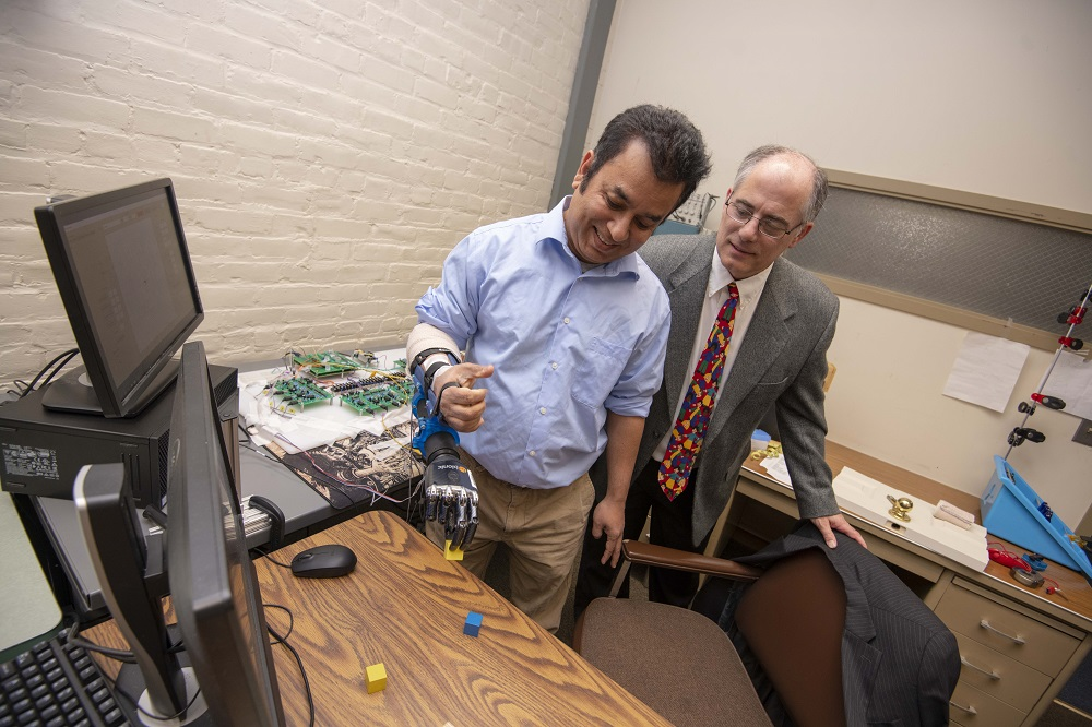 Ted Clancy (right), professor of electrical and computer engineering at WPI, is developing wireless sensors to communicate with a prosthesis.