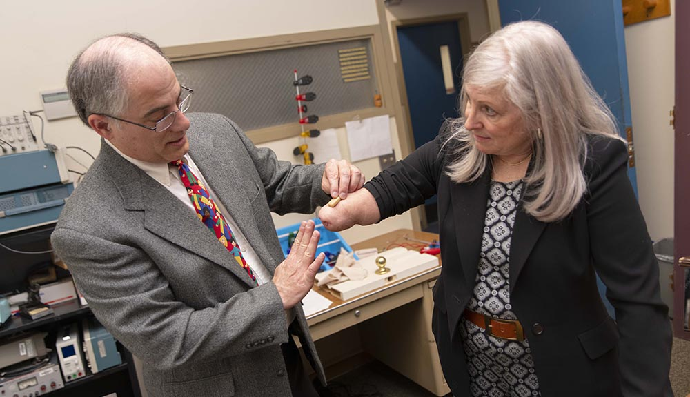 WPI professor Ted Clancy and consultant Debi Latour have had a longstanding partnership on prosthetics research. In this scene, Clancy places a wireless sensor on Latour's arm.