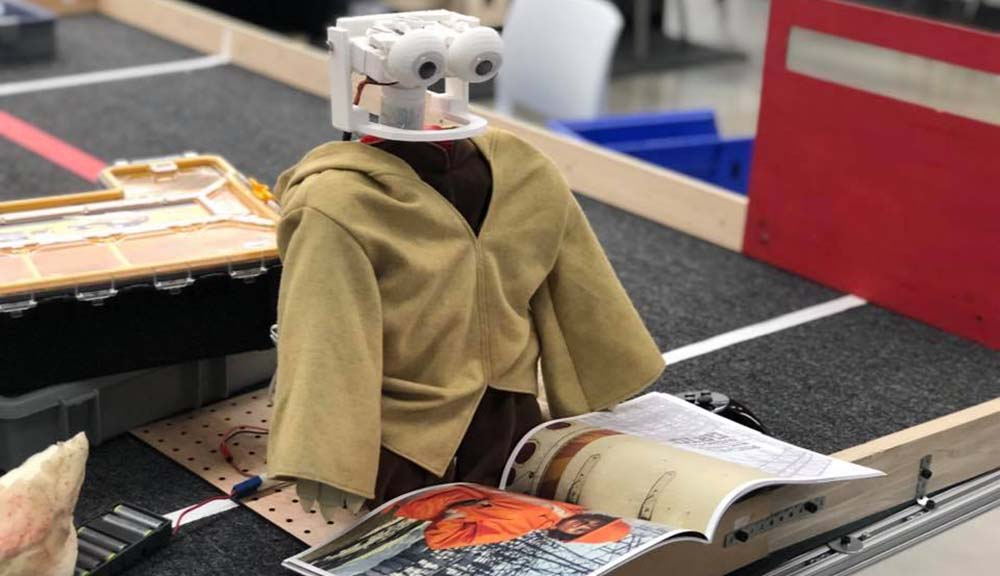"A robot wearing a tan jacket ""reads"" the latest issue of WPI Journal."