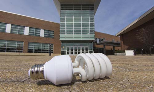 A close-up photo of an energy-efficient lightbulb in front of the Sports & Recreation Center.