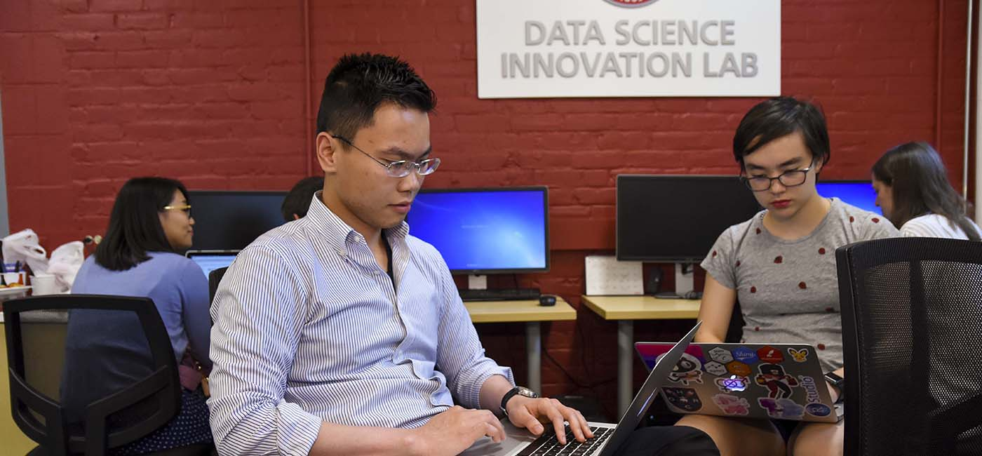 Students sitting in office chairs in front of WPI Data Science Innovation Lab sign
