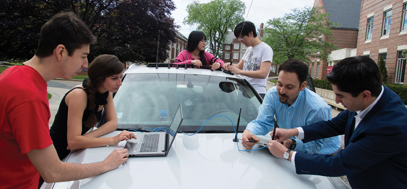 Students working on autonomous car with professor