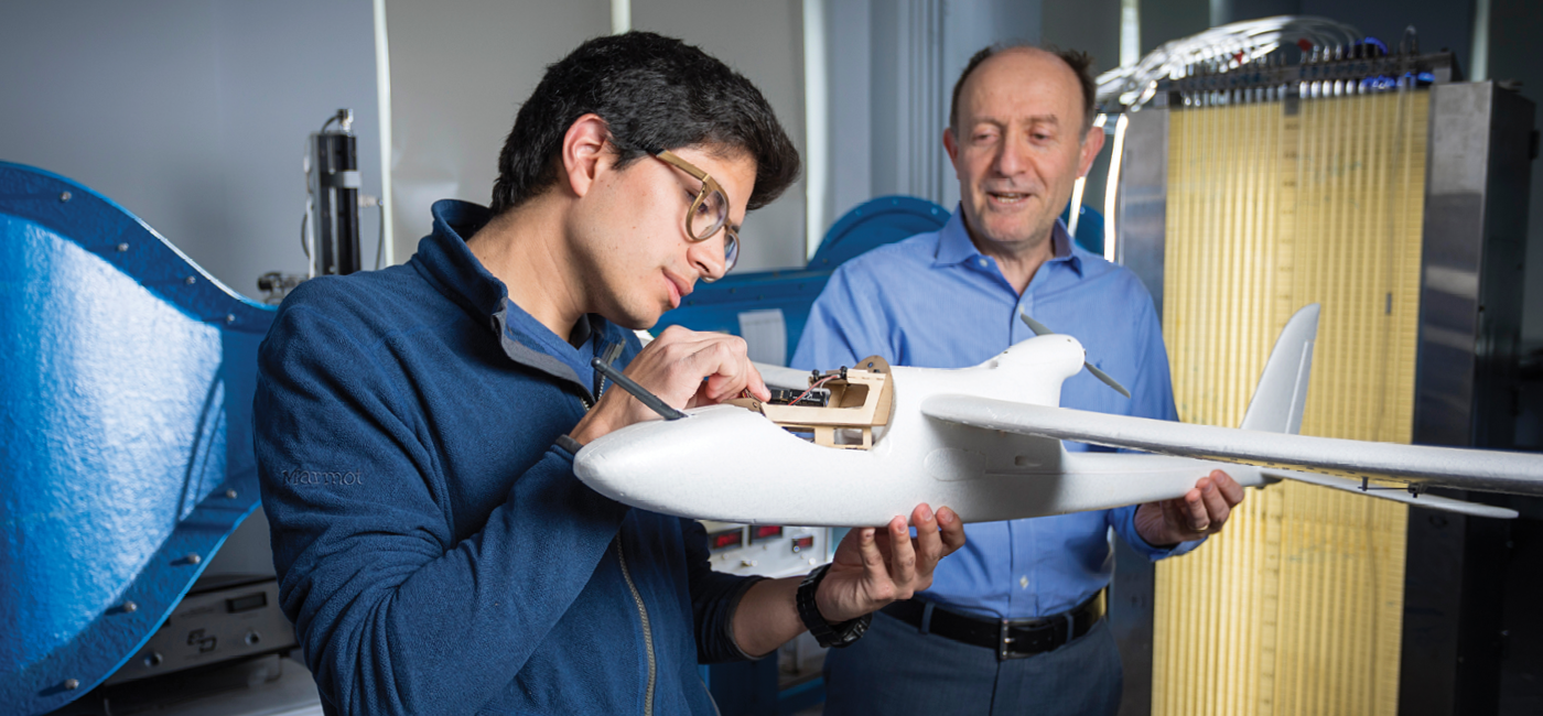 Student examining a model airplane with a professor