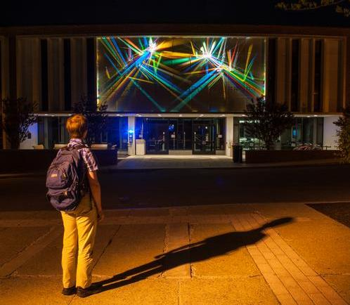 student looking at the brightly colored lightpainting on front of library after dark
