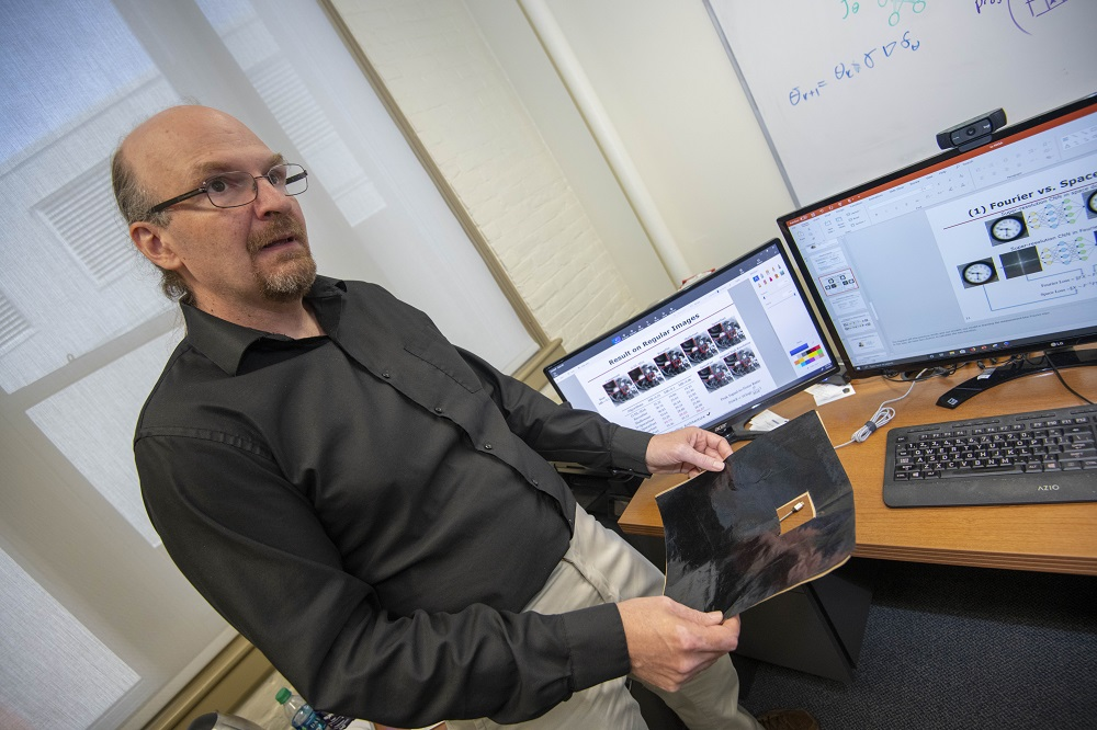 Randy Paffenroth, associate professor of mathematical sciences at WPI, holds a carbon-based sheet known as Miralon®, which is used in a variety of spacecraft applications.