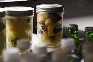 A close-up photo of a variety of fruit inside a clear mason jar.