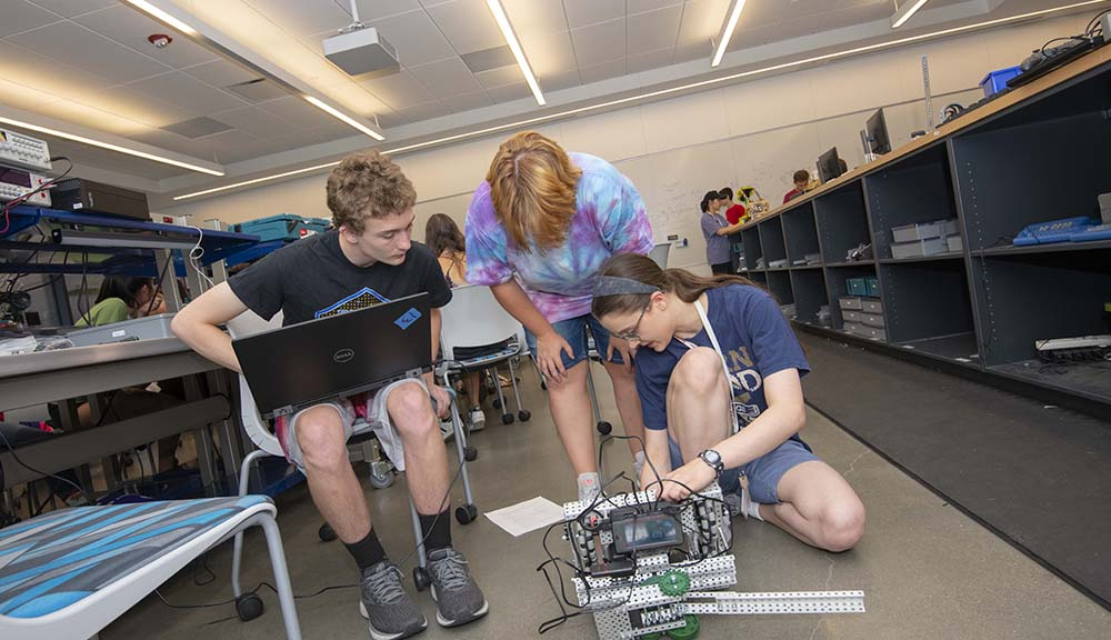 Three students work on a robotics project together. One is holding a laptop, another is adjusting a part of the robot, and the third is overlooking the project.