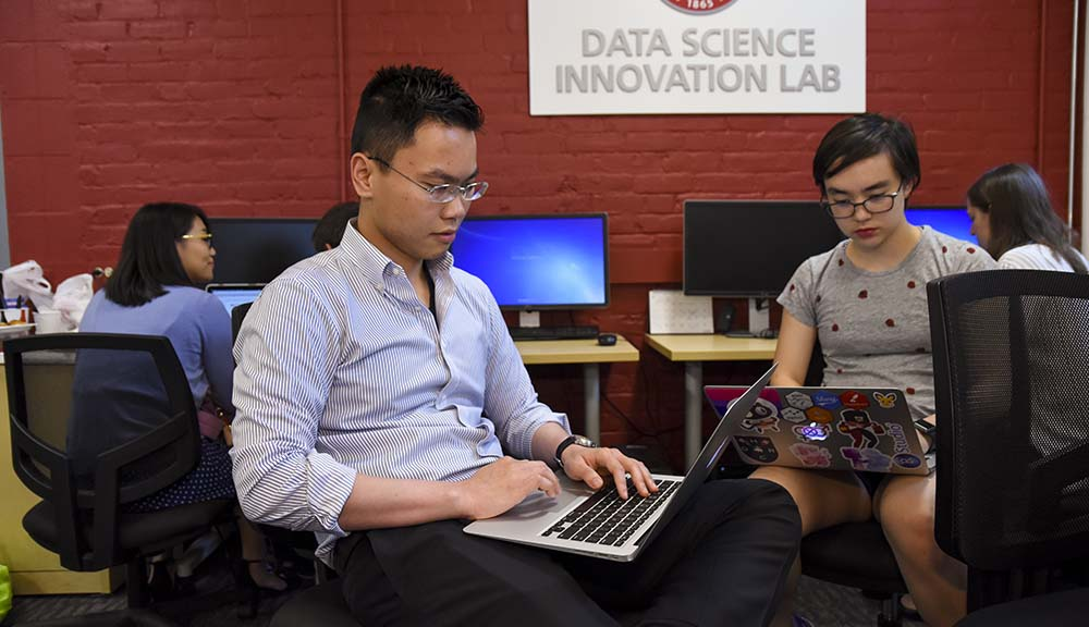 Two students work on laptops in the Data Science Innovation Lab, the WPI seal on a red wall behind them.