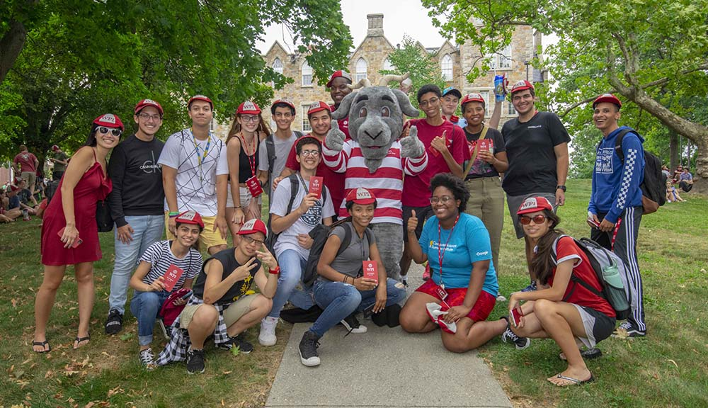 New undergraduate students gather for a group photo with Gompei on Boynton Hill following the Earle Bridge crossing.
