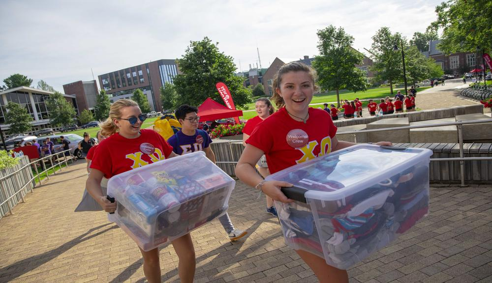 Two students carry in plastic tubs of clothes during Move-In Day.