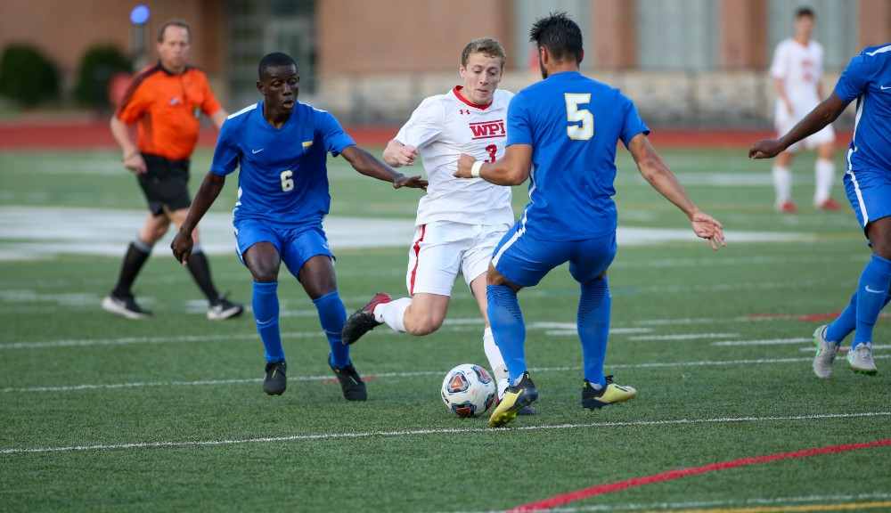 Mark Calnan (center) dribbles the soccer ball past two opposing players in blue uniforms.