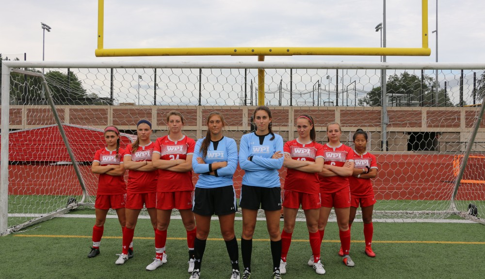Senior members of the women's soccer team stand together in front of the goal.