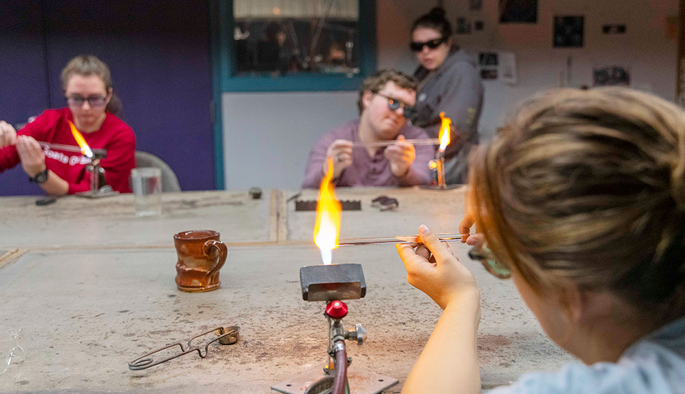 Student working with smelting tools