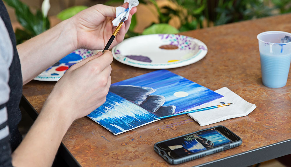 Student painting a picture displayed on a smartphone