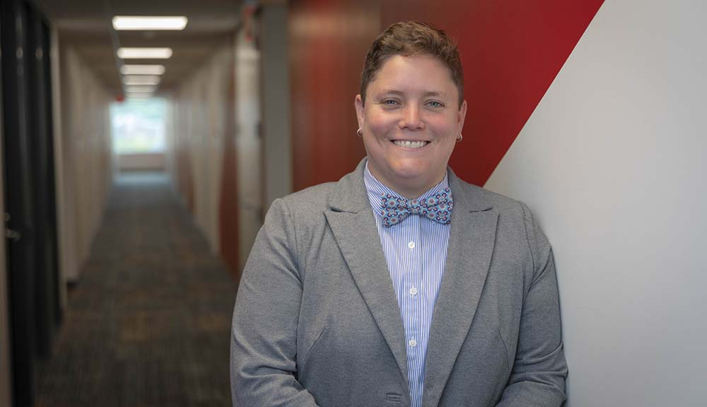 Casey Wall smiles in front of a hallway in the Messenger Residence Hall. She's smiling and is wearing a gray blazer, blue button-up shirt, and blue bow tie.
