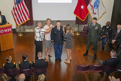 Connor Sakowich being pinned by his parents, Julie and Rich Sakowich, and girlfriend, Victoria Nassar, as his friend, Army Cpl. Jake Zwart stands at right. alt