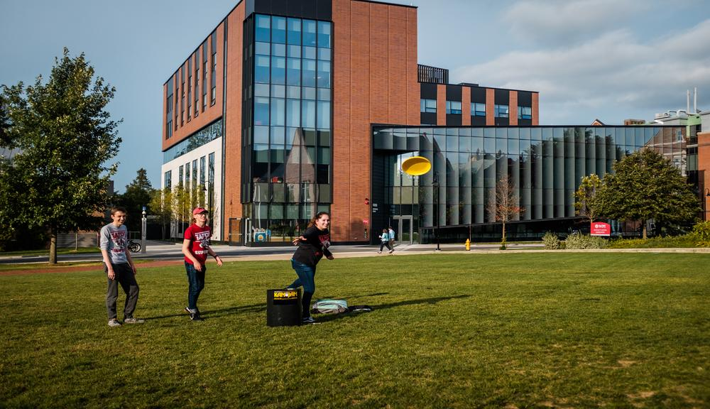 Students play frisbee on the Quad with the Foisie Innovation Studio in the background.