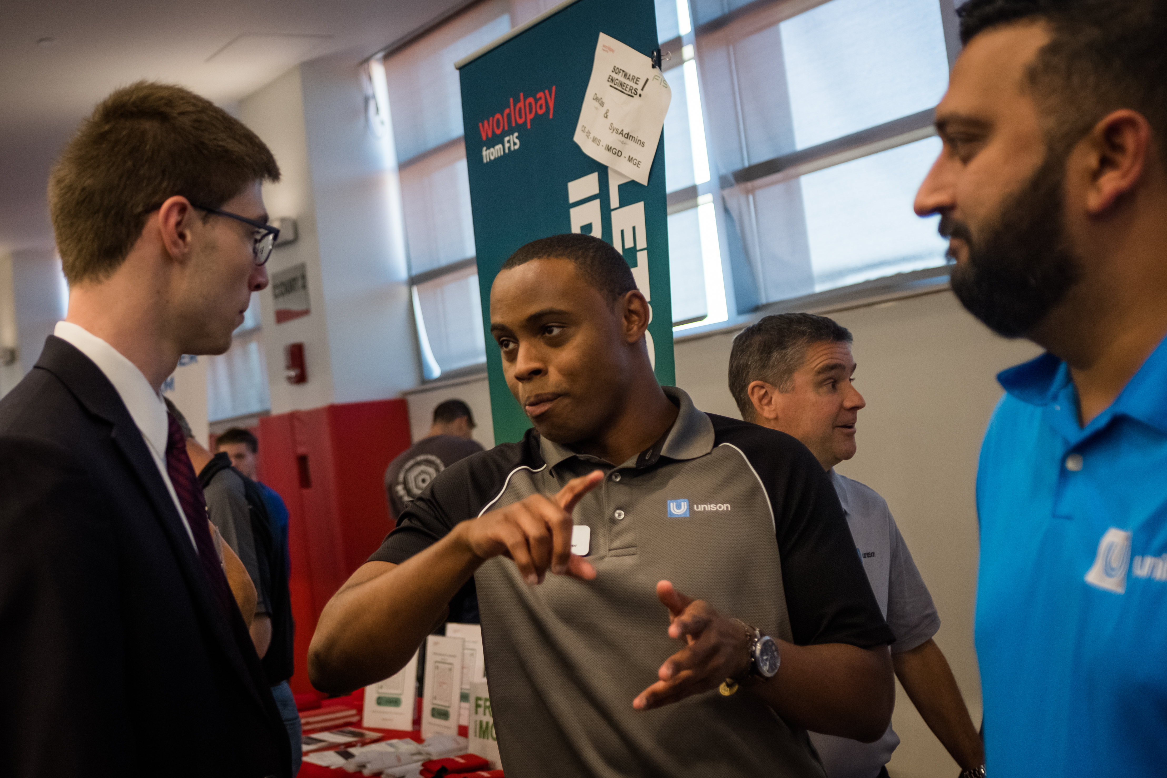 Employers discuss their companies with an interested WPI student during the Fall Carer Fair.