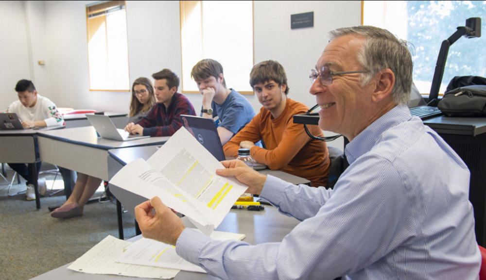 Craig Putnam sits in one of his classes with students' desks arranged in a circle. He's smiling and is holding several papers in his hands.