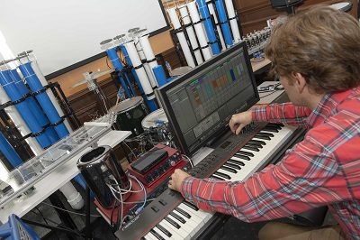 Professor Scott Barton adjusts a musical robot, which musicians will interact with during the concert.  alt
