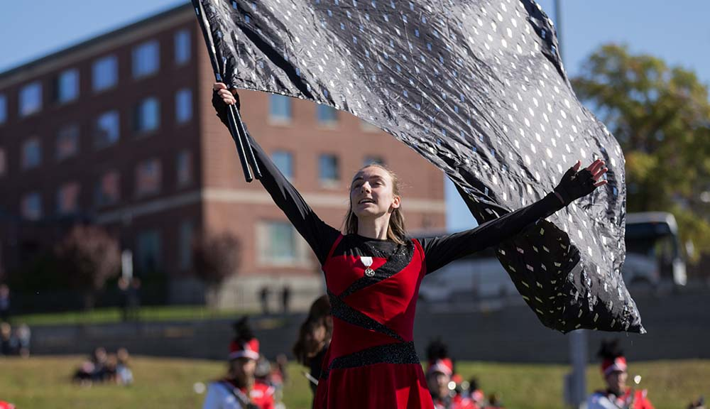 A member of the WPI color guard performs during Homecoming 2019.