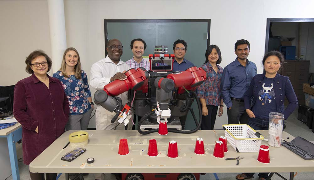 WPI researchers gather with a robot being used to study human-robot interaction in the workplace.