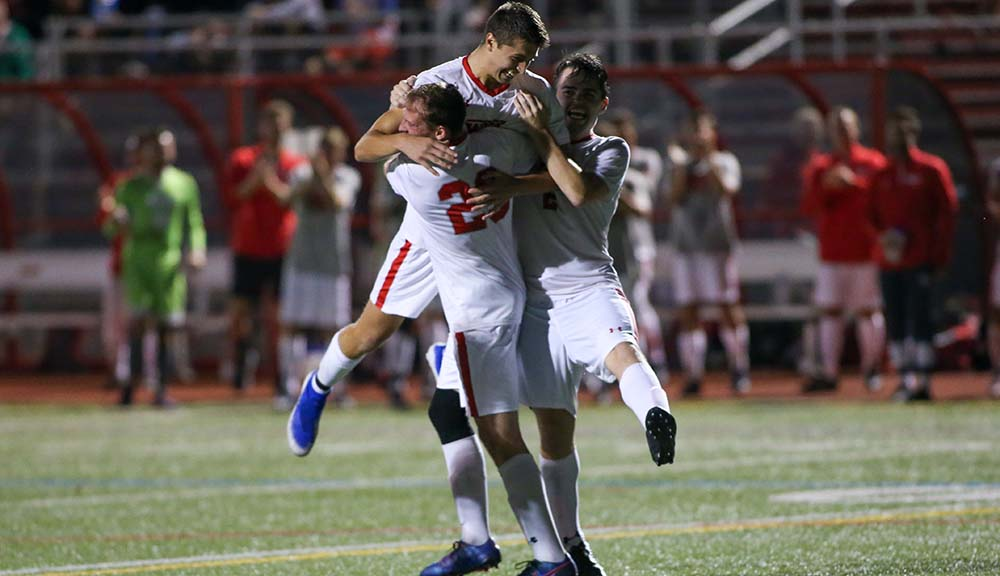 Three members of the men's soccer team celebrate on the field.