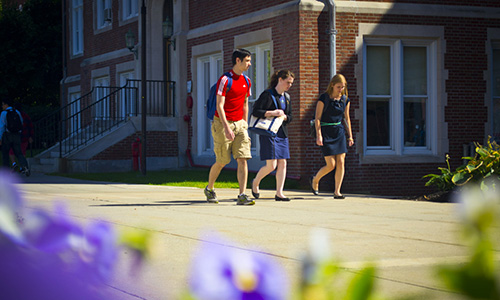 three students walking across a sunny campus