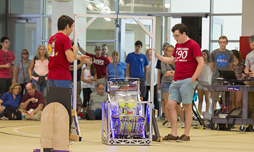 Group of WPI students displaying a robot to a crowd of parents and other students.
