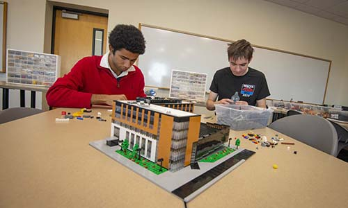 Two members of the LEGO Club work on a project. alt