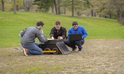 three male students working with a drone