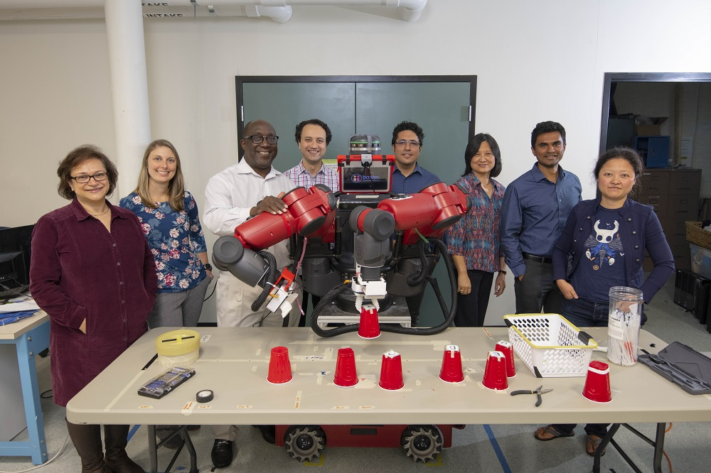 WPI researchers (from left) Soussan Djamasbi, Jeanine Skorinko, Winston Soboyejo, Cagdas Onal (principal investigator), Yunus Telliel, Jing Xiao, Pratap Rao and Jane Li with the Baxter research robot.