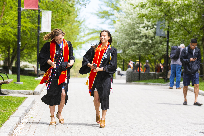 Two WPI female graduates walking on WPI campus