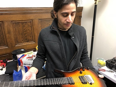 WPi professor holding electric guitar