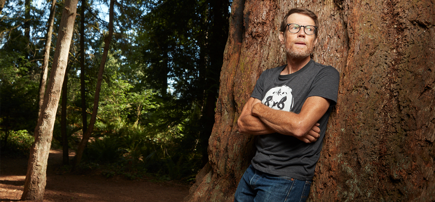 Christopher James leaning against a large tree in a forest.