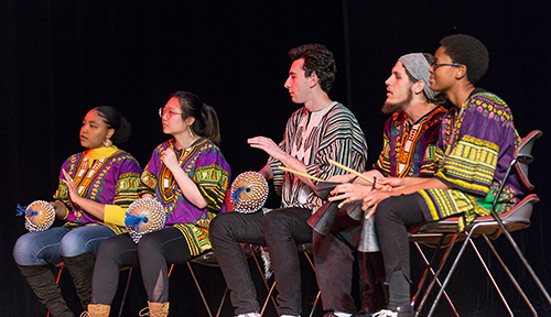Members of OMA performing with instruments on stage at international dinner