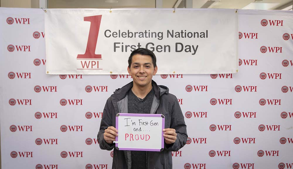 "A student stands in front of a WPI banner with a sign that reads ""I'm First Generation and Proud."""