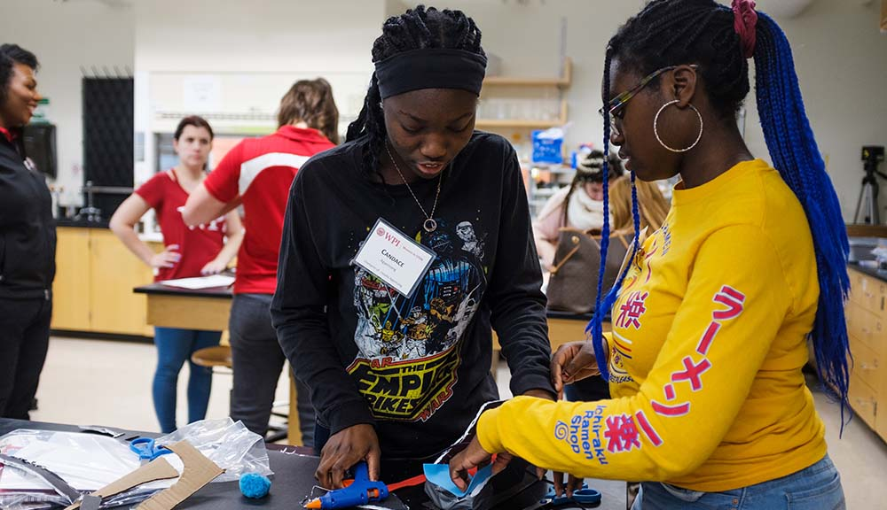 Two participants at the Women in STEM Conference work on a project in the lab together.