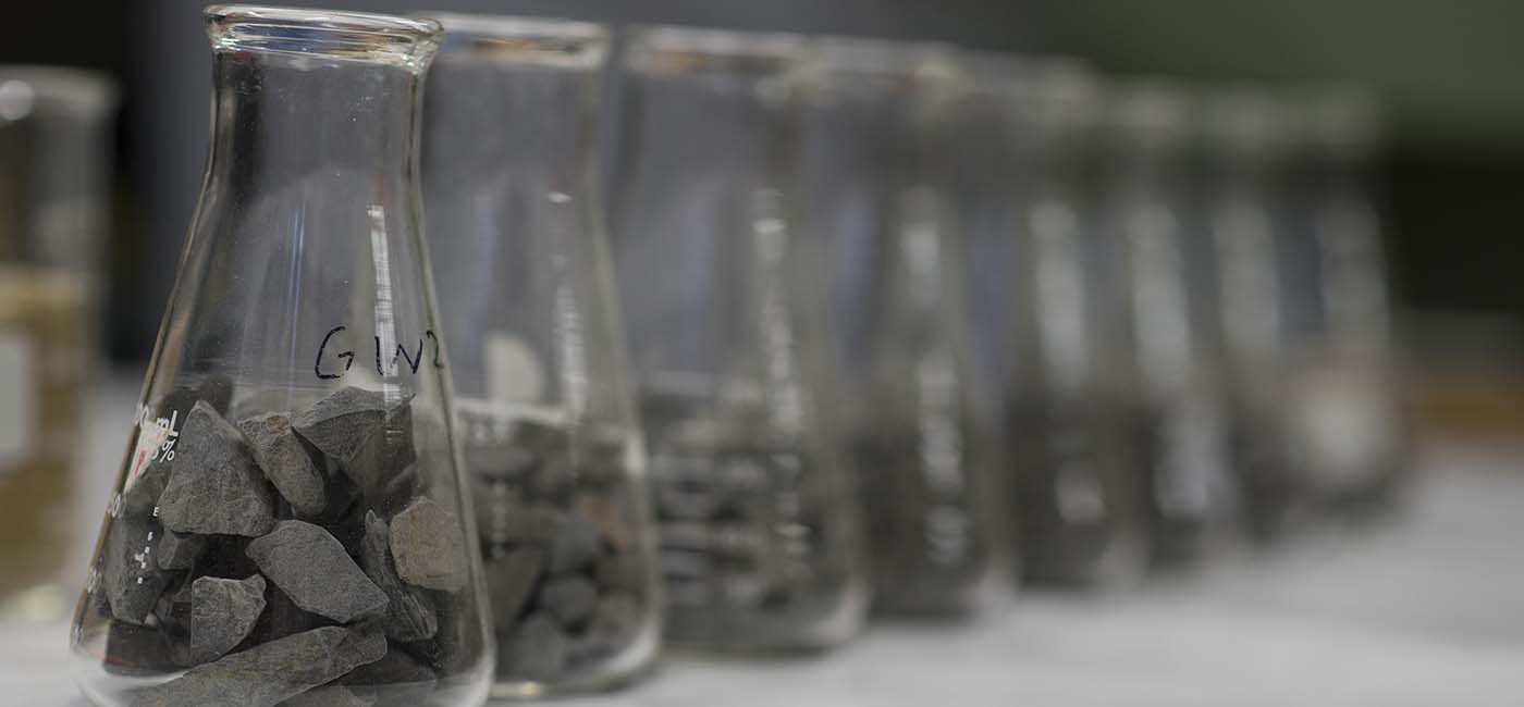 A line of beakers containing rocks