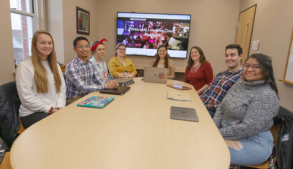 "Students and faculty gather around a table with a screen displaying ""Wearable Learning Cloud Platform"" on it behind them."