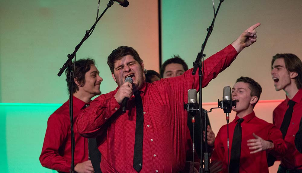 A student in a red dress shirt and black tie sings into a microphone while pointing up at the sky.