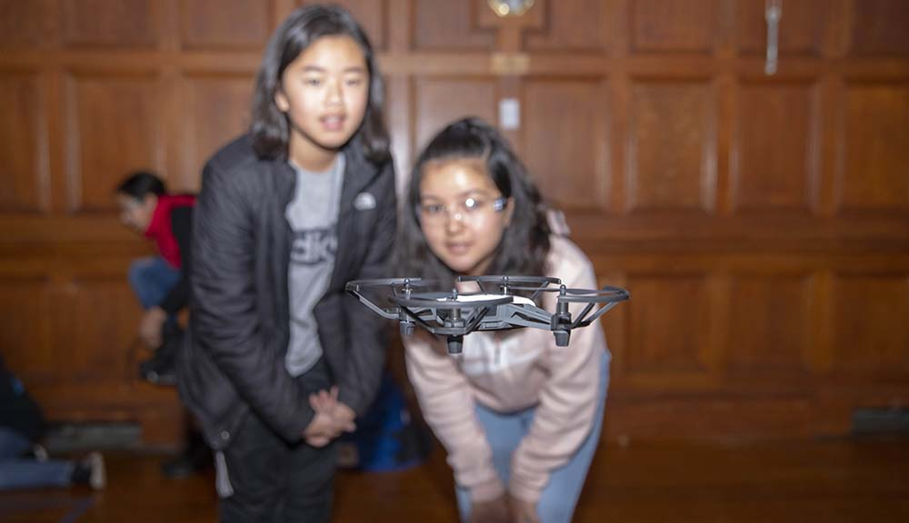 Two students check out a drone flying in front of them. The drone is in focus.