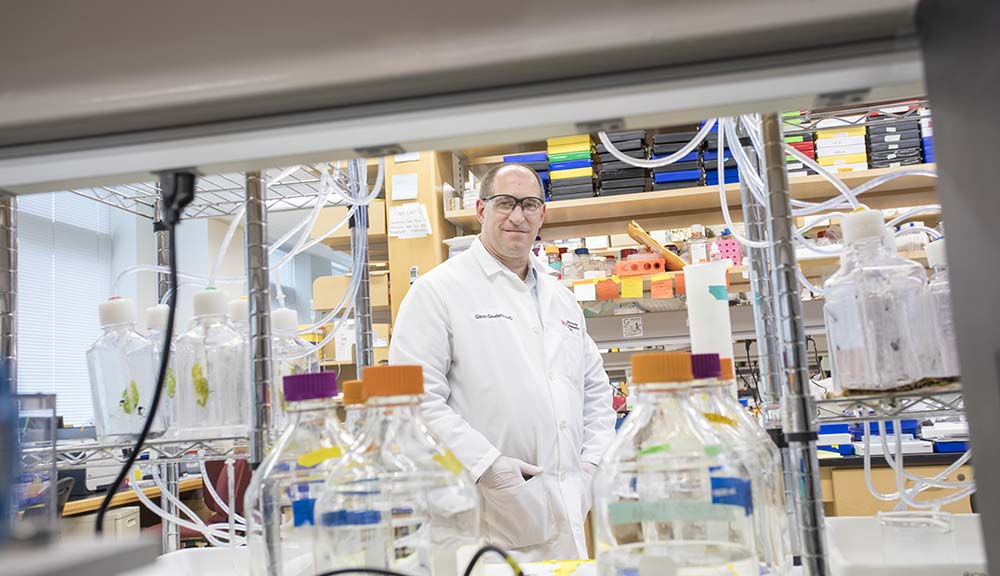 Glenn Gaudette poses in the lab in safety glasses and a white lab coat, smiling through a break in some shelving.