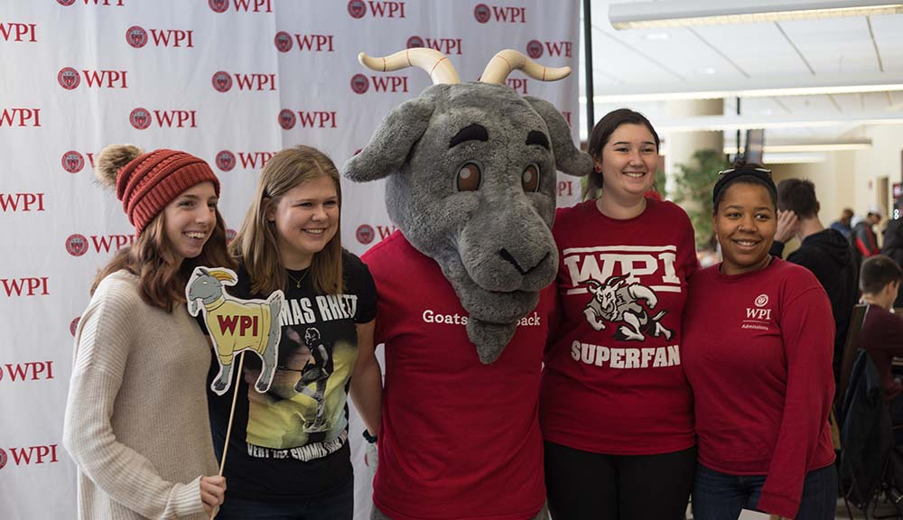 Students wearing WPI gear pose with Gompei in front of a step-and-repeat banner in the Rubin Campus Center.