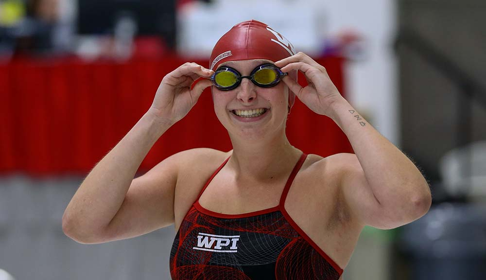 Jillian Clemente '20 smiles for the camera wearing her swimsuit, swim cap, and goggles.