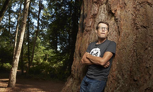 WPI alumnua Christopher James leaning on tree
