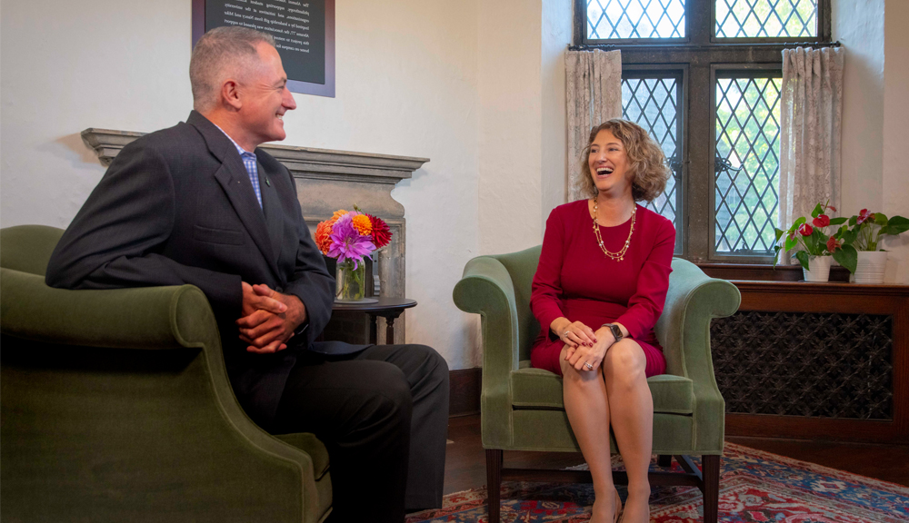 Mark Macaulay and President Laurie Leshin laugh together during an interview
