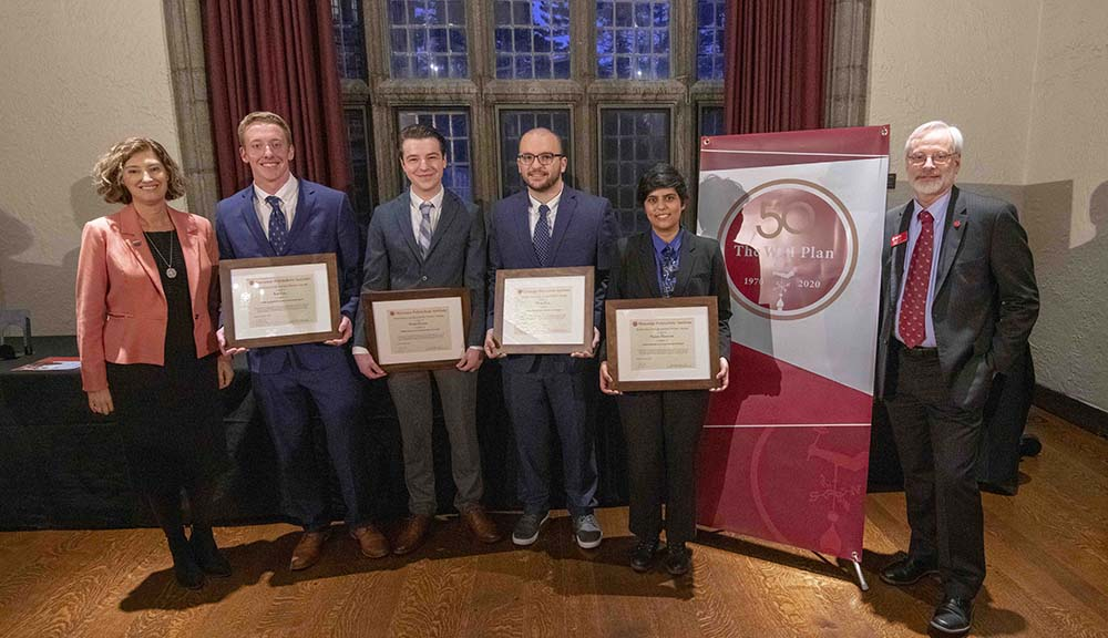 The four members of the winning President's IQP Award team stand between Laurie Leshin and Kent Rissmiller holding their certificates.
