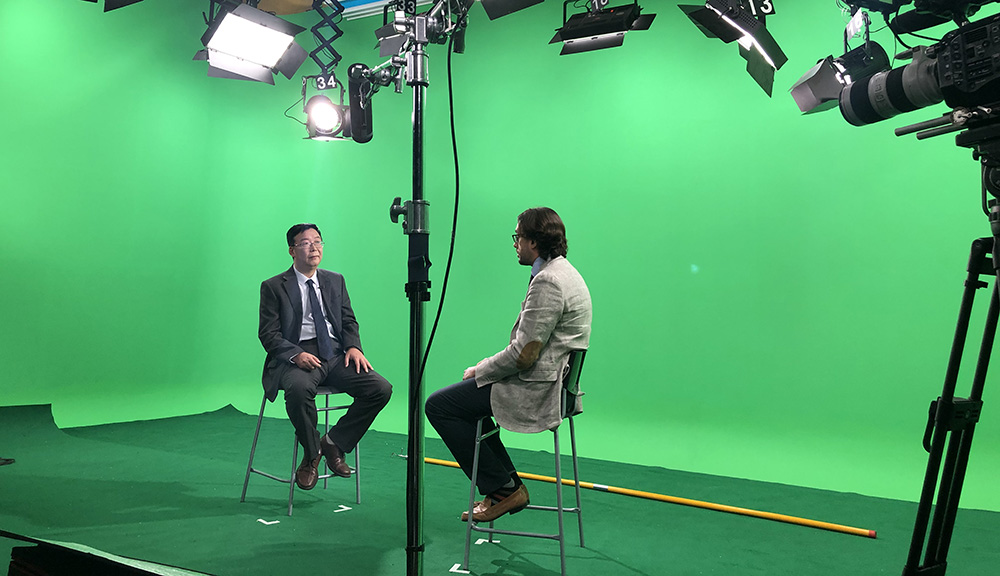 Professor Pincirolli being interviewed with a green screen in the background.